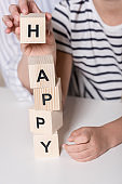 Girl composing word Happy using wooden cubes