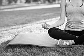 Young woman practicing yoga outdoors at the park