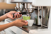 Cropped shot of female barista using coffee machine while making coffee in cafe