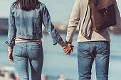 couple holding hands outdoors at riverside