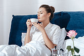 Young woman having morning coffee in bed