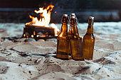 bottles of beer standing on sandy beach with bonfire behind
