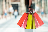 Cropped shot of man holding multicolored paper bags while standing in shopping mall