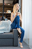 Young gorgeous blonde woman with coffee near window in living room