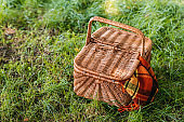 top view of wicker picnic basket with rug on green grass