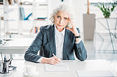 portrait of senior businesswoman sitting at workplace and signing contract