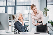 Young businesswoman showing laptop to senior colleague sitting at workplace