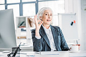 Smiling senior businesswoman drinking coffee and showing ok sign at workplace