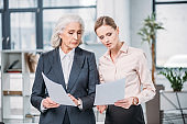 Two serious businesswomen standing and holding documents in office