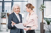 Young businesswoman holding document and looking at smiling senior colleague