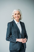 portrait of smiling senior businesswoman in suit isolated on grey