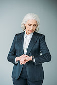 focused senior businesswoman checking time on watch isolated on grey