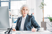 Confident senior businesswoman sitting at workplace and writing with pen
