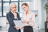 Two serious businesswomen standing and holding document in office