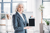 Smiling senior businesswoman standing in office and holding digital tablet with blank screen