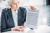 portrait of serious businesswoman sitting at workplace and pointing at contract