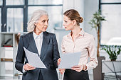 Serious businesswomen standing and holding documents and looking at each other