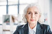 Close-up portrait of beautiful senior businesswoman looking at camera