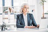 portrait of confident businesswoman typing on laptop at workplace in modern office