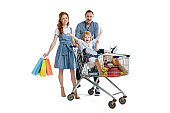 Happy young parents with paper bags carrying cheerful little son sitting in shopping trolley