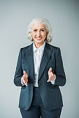 smiling senior businesswoman with extended hands isolated on grey