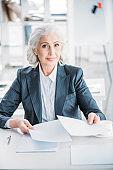 portrait of confident senior businesswoman doing paperwork at workplace