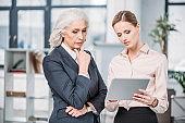 Two serious businesswomen in formal wear using digital tablet in office
