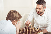 little boy playing chess together with smiling father at home