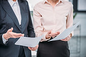Close-up partial view of two businesswomen in formal wear holding papers