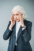 senior businesswoman in suit having headache isolated on grey