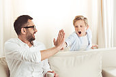 father drinking coffee and giving high five to his little son at home
