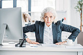Confident aggressive senior businesswoman sitting at workplace and looking at camera