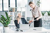 young businesswoman and her boss working with laptop computer and documents in office