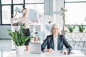 smiling businesswoman sitting at workplace in office, stressed colleague with documents behind