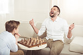 man celebrating win in chess game with upset son near by