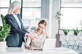 young stressed businesswoman and her boss working with laptop computer in office