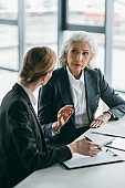 two businesswomen with clipboard discussing business project on meeting in office