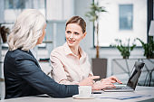 Smiling businesswomen talking while using laptop at workplace