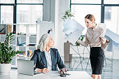 young stressed businesswoman with documents arguing at colleague sitting at workplace in office