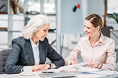 two happy businesswomen discussing business project on meeting in office