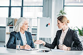 two businesswomen gesturing and discussing business project on meeting in office
