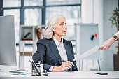 Serious senior businesswoman looking at hand holding paper