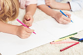 cropped shot of kids writing with felt pens on blank paper sheet at home