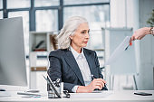 shocked senior businesswoman looking at documents while sitting at workplace in office
