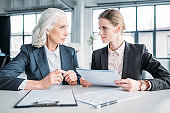two serious businesswomen with documents discussing business project on meeting in office