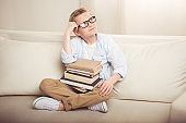 Thoughtful little boy in eyeglasses sitting on sofa with pile of books and looking away