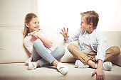 cheerful sister and brother talking together while sitting on sofa at home