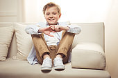 smiling caucasian boy wearing casual clothing while looking at camera and sitting on sofa at home
