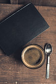 Glass of coffee drink, old book and spoon on rustic wooden table