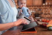 woman and baby boy shopping online with digital tablet